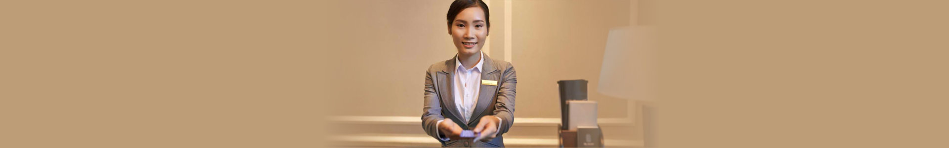 smiling receptionist giving electronic key to the guest